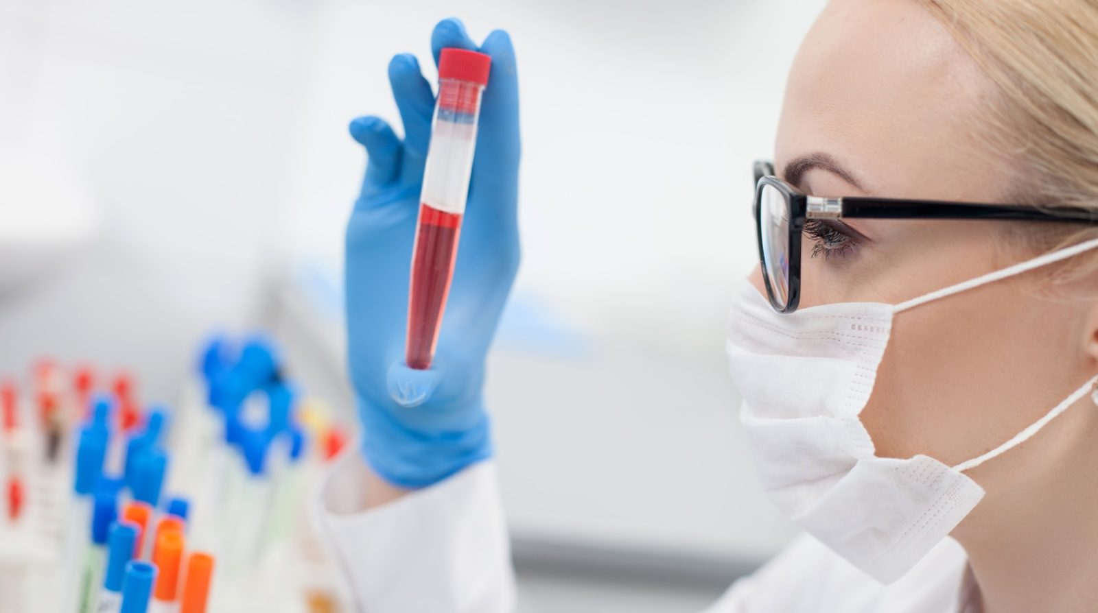 Professional female researcher is making experiments with human blood. She is holding a flask and looking at it with seriousness. The woman is standing in profile with mask and eyeglasses
